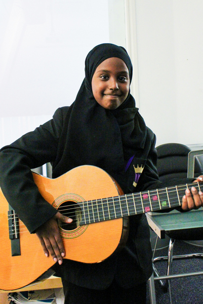 ARK Kings Academy Band Musicianship student Sheima with acoustic guitar