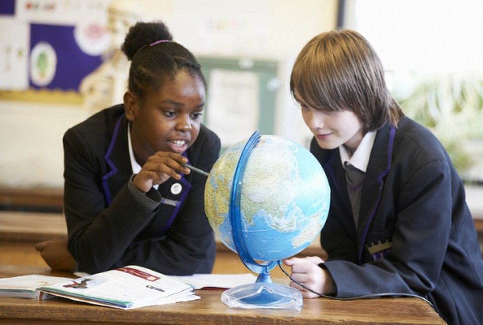 ARK Kings Academy students looking at a globe in a Geography lesson