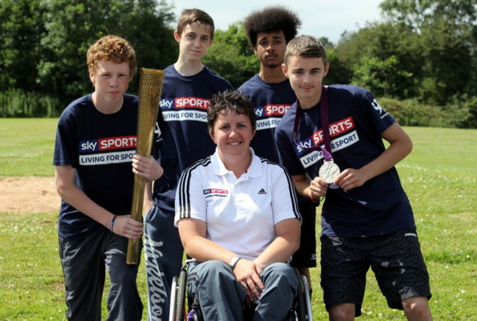 Paralympics medal winning archer Mel Clarke posing with her London 2012 torch and silver medal with students from ARK Kings Academy in Birmingham