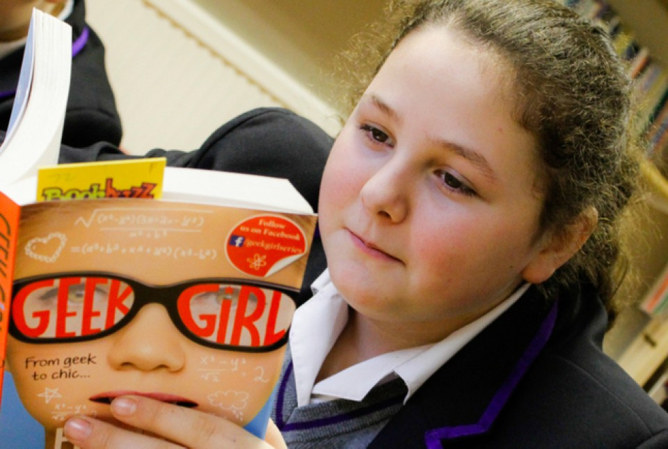 ARK Kings Academy females student reading a book in the school library